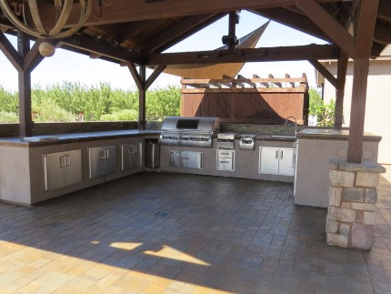 Picture of a stamped concrete patio and concrete countertop installed underneath a patio cover held up by stacked stone pillars. There is a barbecue and sink installed into the countertop
