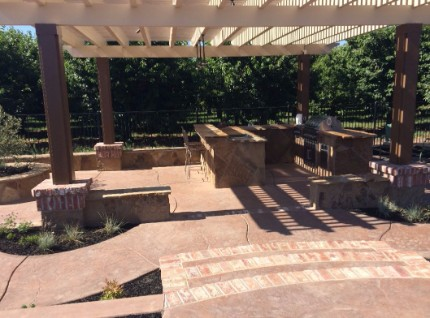 picture of a concrete patio area with concrete countertop installed as well as pillars that hold up a patio cover
