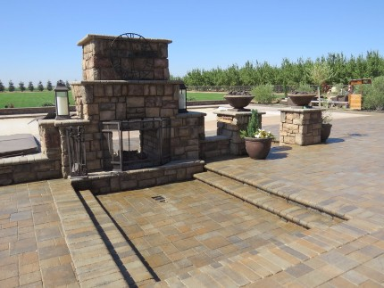 picture of a beautiful stacked stone fireplace in front of a concrete patio and stone wall in the back